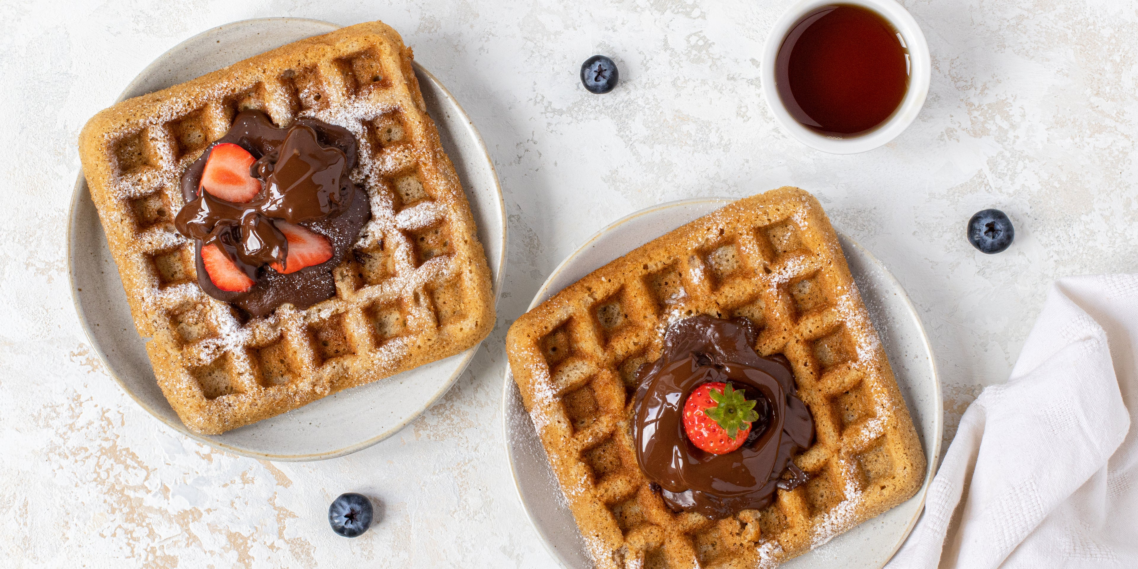 Top view of Waffles dusted in icing sugar, topped with chocolate sauce and strawberries