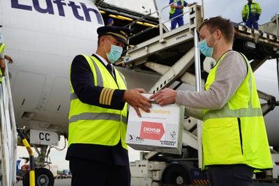 Übergabe der Transportbox vor der Maschine der Lufthansa Cargo