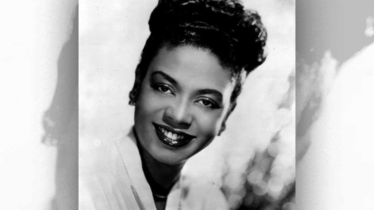 A black and white profile shot of Hazel Scott smiling.