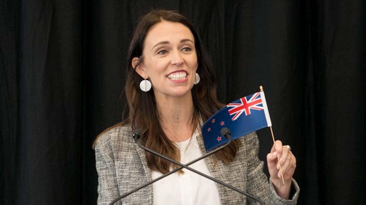 An image of Jacinda Ardern waving the New Zealand flag.
