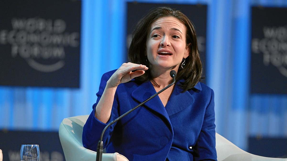An image of Sheryl Sandberg speaking on a stage.
