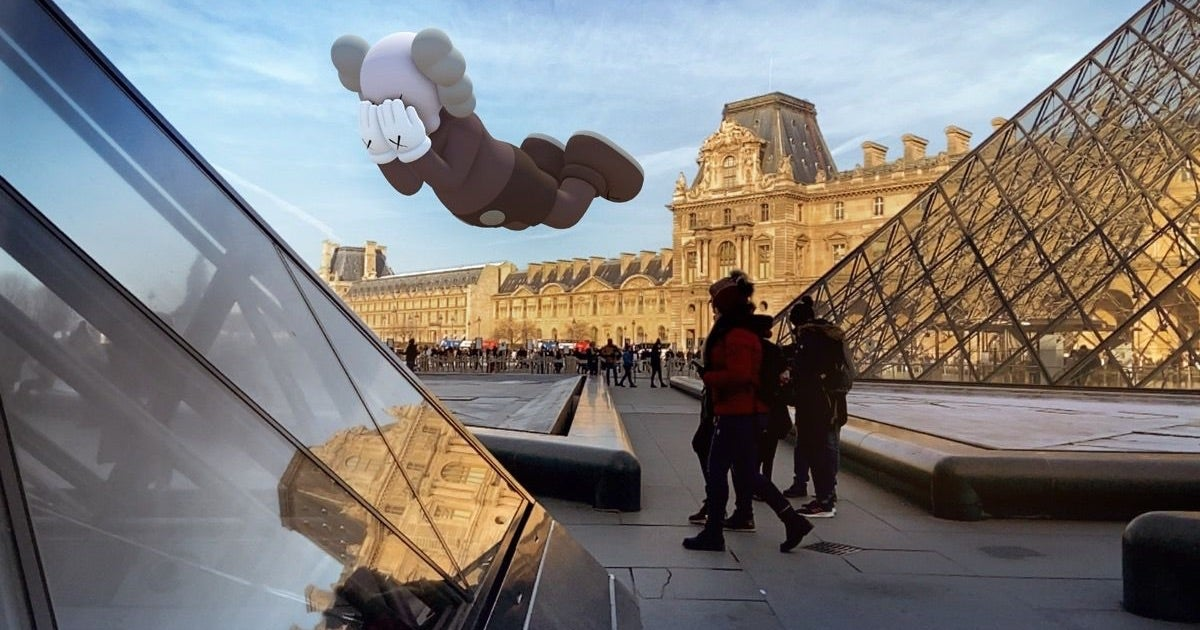 image shows the exterior of the Louvre in Paris with a Kaws statue AR floating above the ground