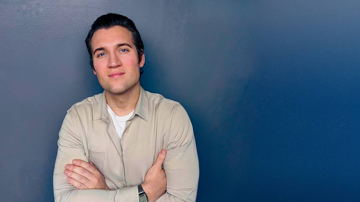 Profile shot of Paul Norris in front of blue background