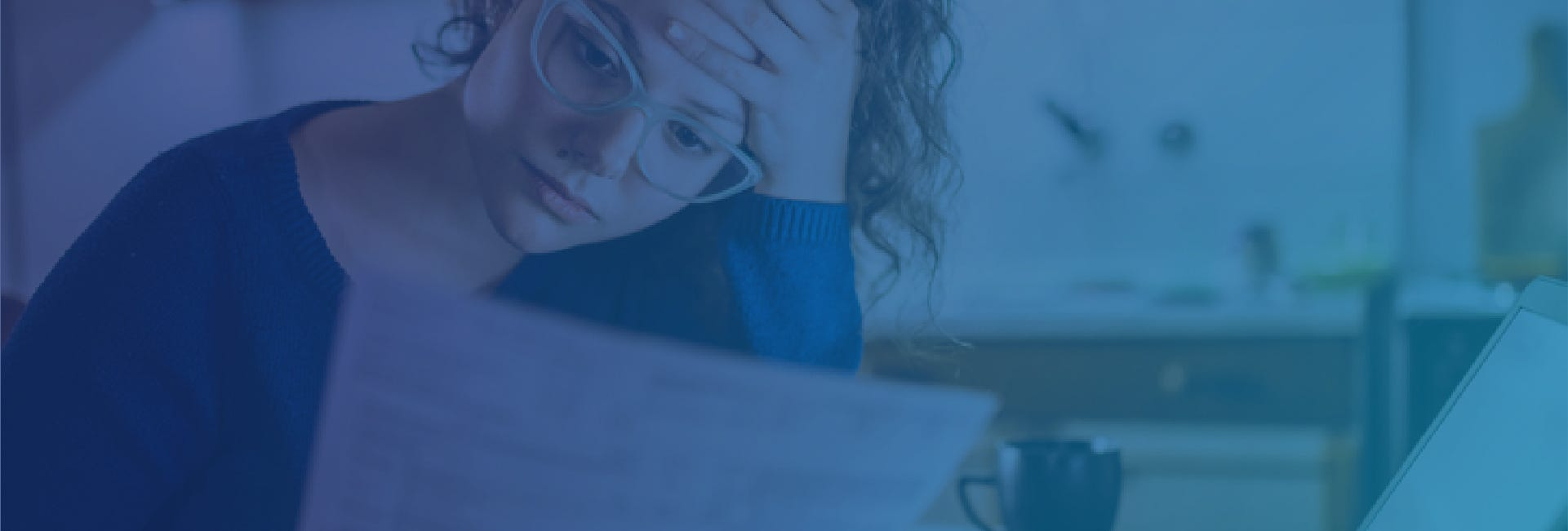 Woman wearing glass and looking unhappily at a document as she has business stress