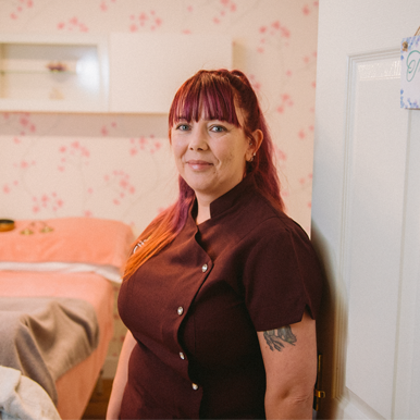 Alison from New Moon Holistic Therapies stands in the doorway of her treatment room