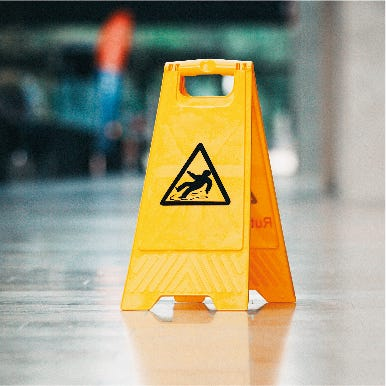 Yellow wet floor warning sign with image of slipping person in black triangle