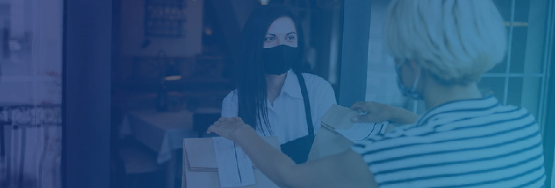 Woman wearing face mask taking two bags of takeaway food from restaurant worker wearing apron and face mask
