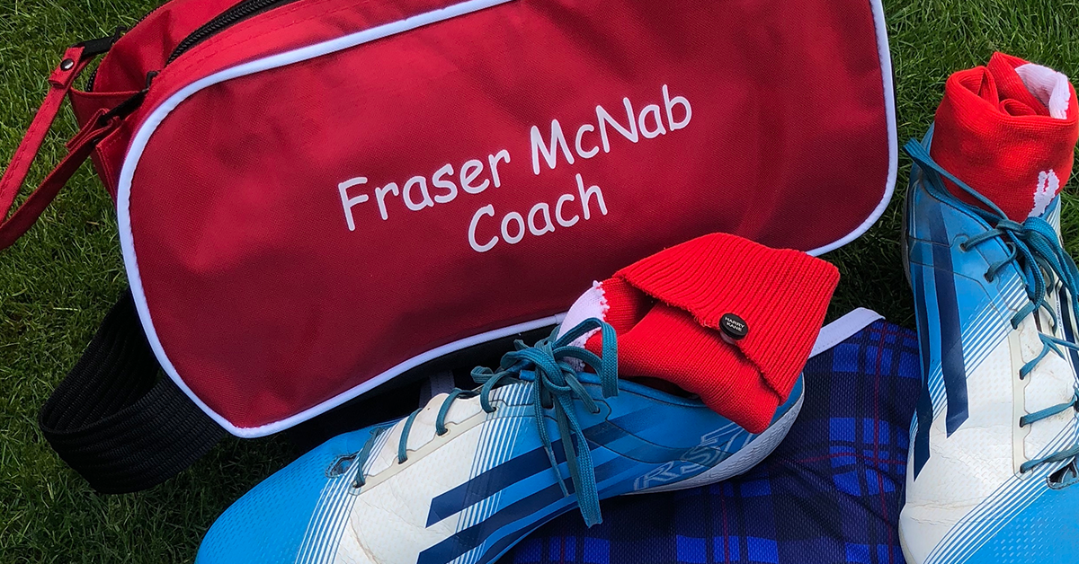 Red football boot bag next to some football boots and socks with Labels4Kids name labels on