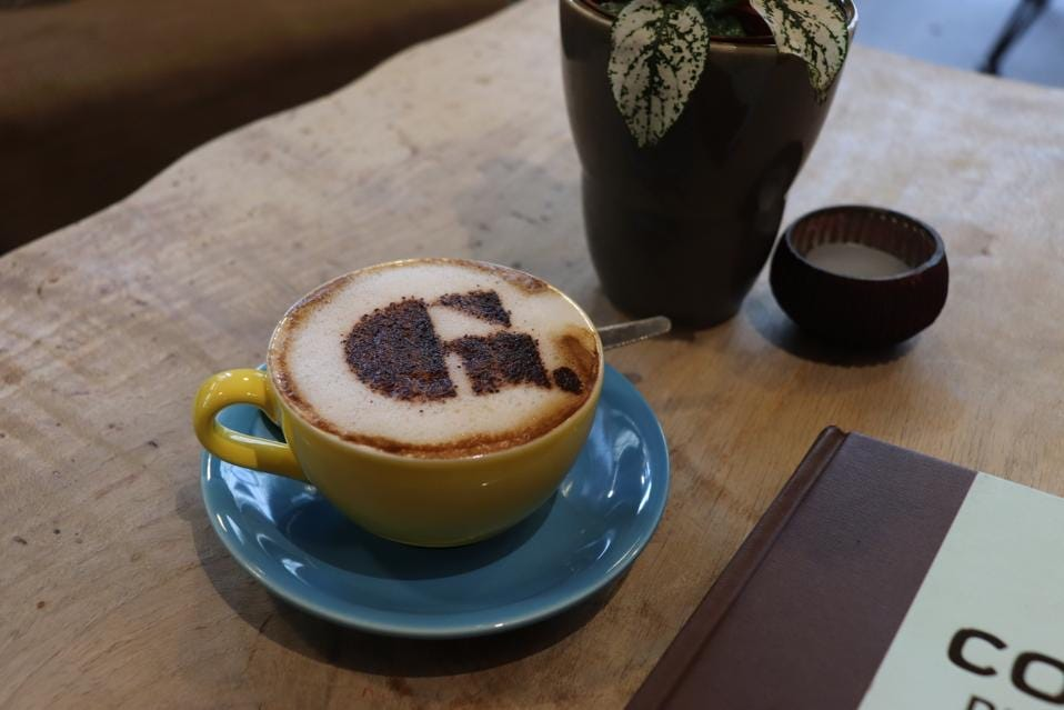 Yellow coffee cup on blue saucer on wooden table. Coffee cup has frothy cappuccino with Goupie logo on top in chocolate.