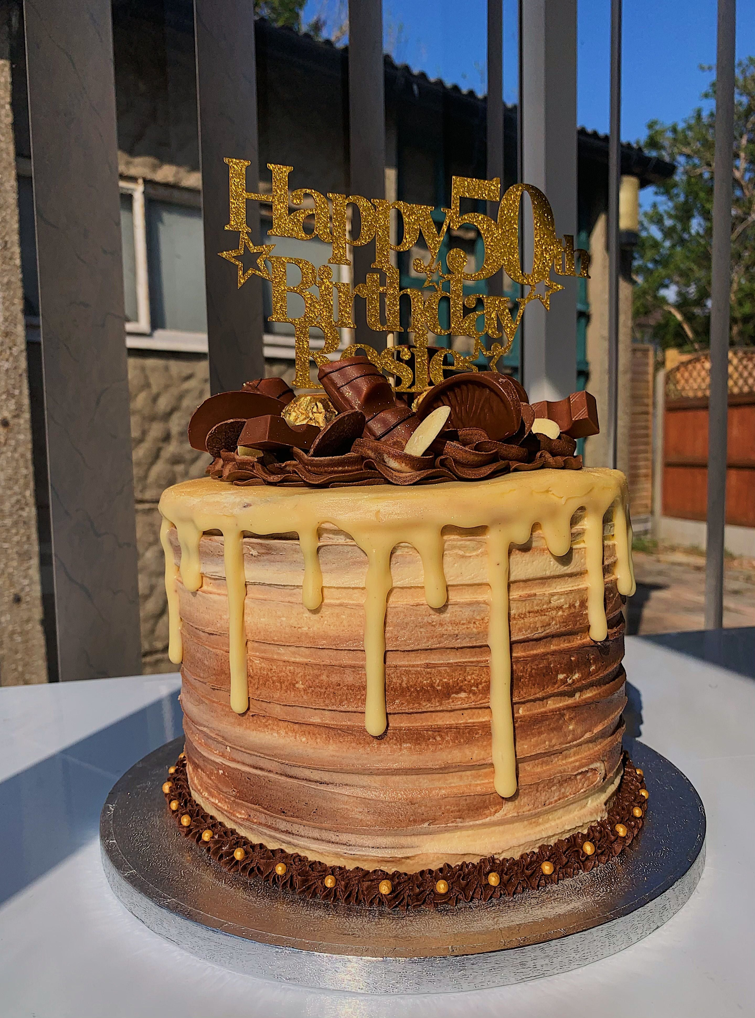 Chocolate cake decorated with Kinder and Ferrero chocolates and Happy 50th Birthday on top