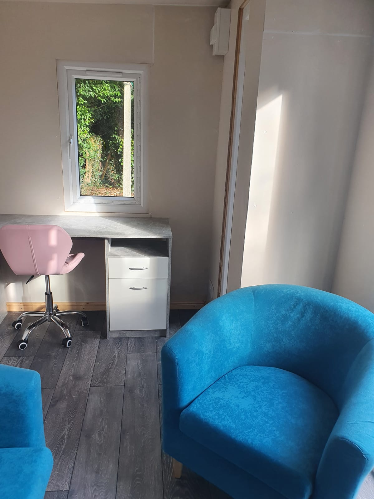 The inside view of the office, complete with two blue chairs and a desk