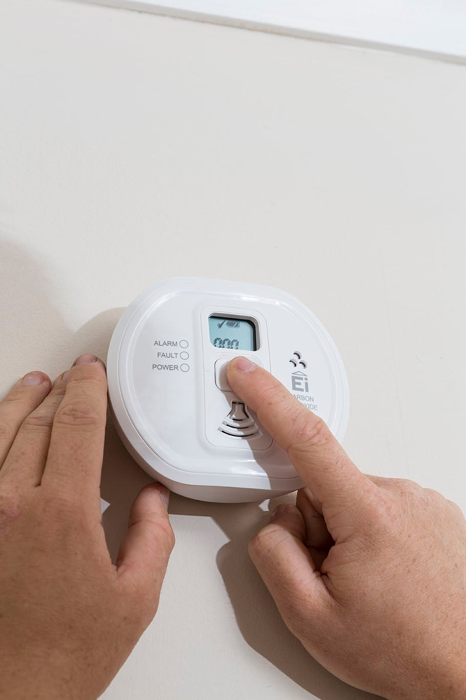 A man presses a button on a carbon monoxide alarm to check it is working