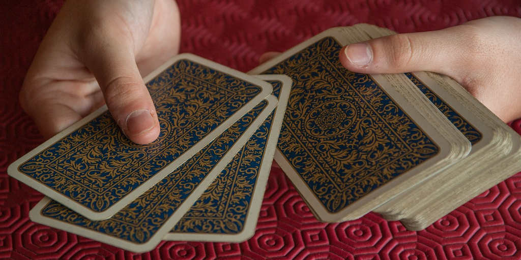 Hands holding a pack of tarot cards