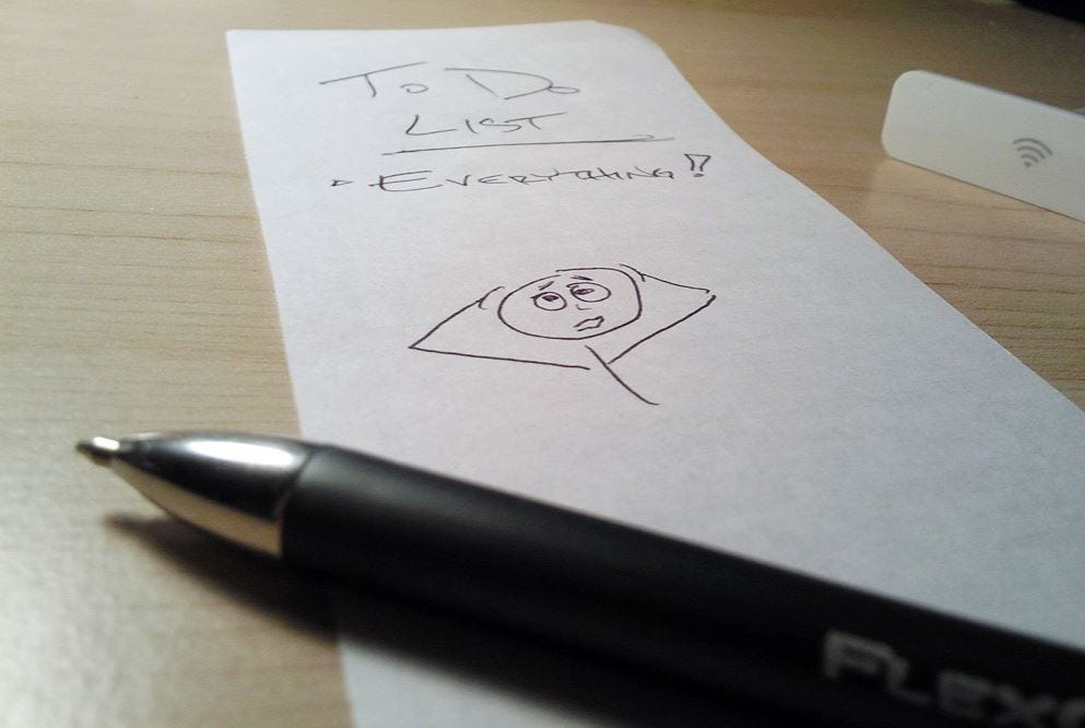 Black pen next to white paper. On it is written 'to-do list. Everything' and drawing of worried stick man.