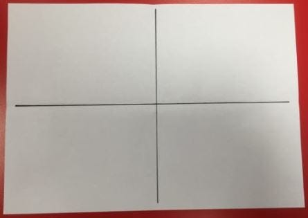 Red table with white sheet of paper. Paper has one black horizontal and one black vertical line drawn down the middle as a cross