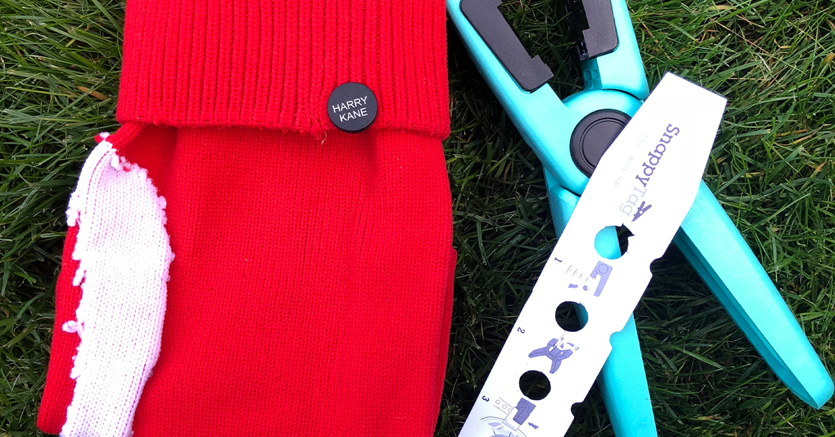Red football sock  with black button attached with the name of HARRY KANE.