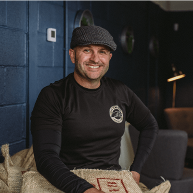 Mark Hepworth of Flat Cap Coffee Roasting Co. sat on bag of coffee beans