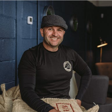 Mark Hepworth of Flat Cap Coffee Roasting Co. sat on bag of coffee beans
