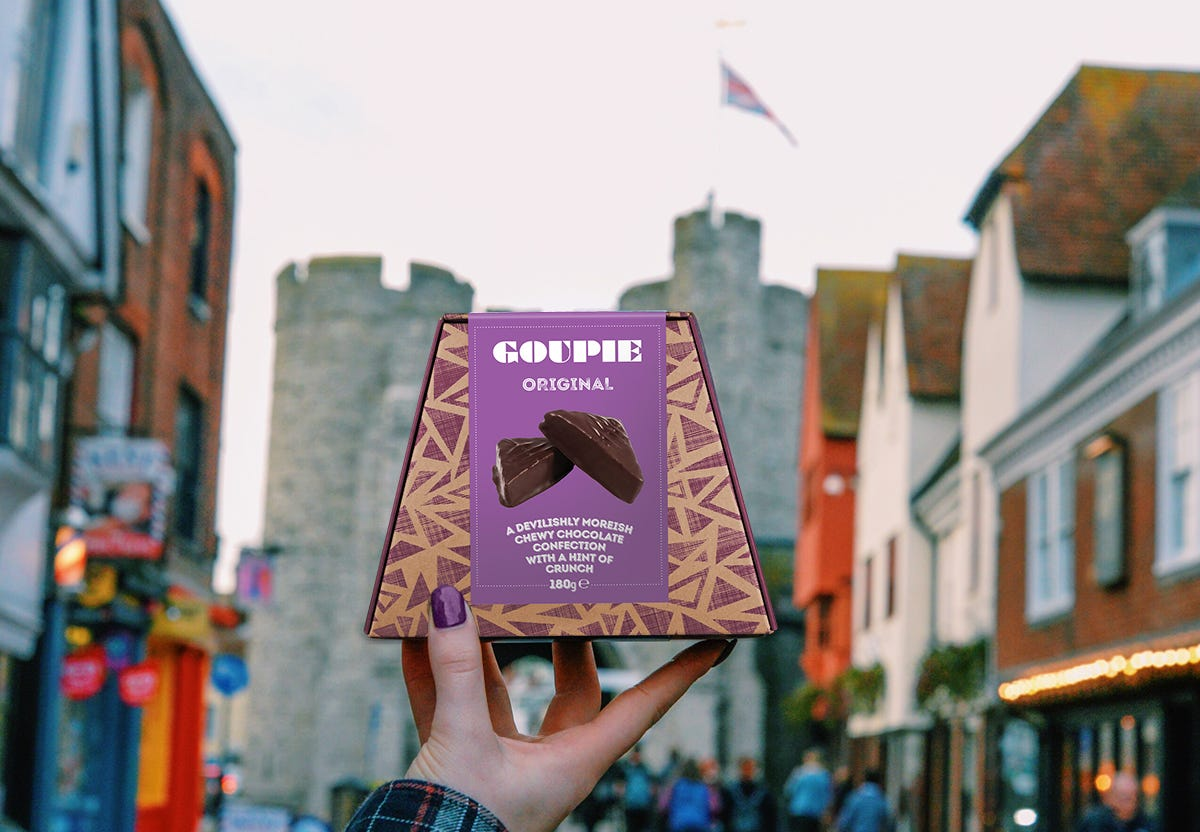 Box of Goupie chocolate being held up on high street in front of a castle.