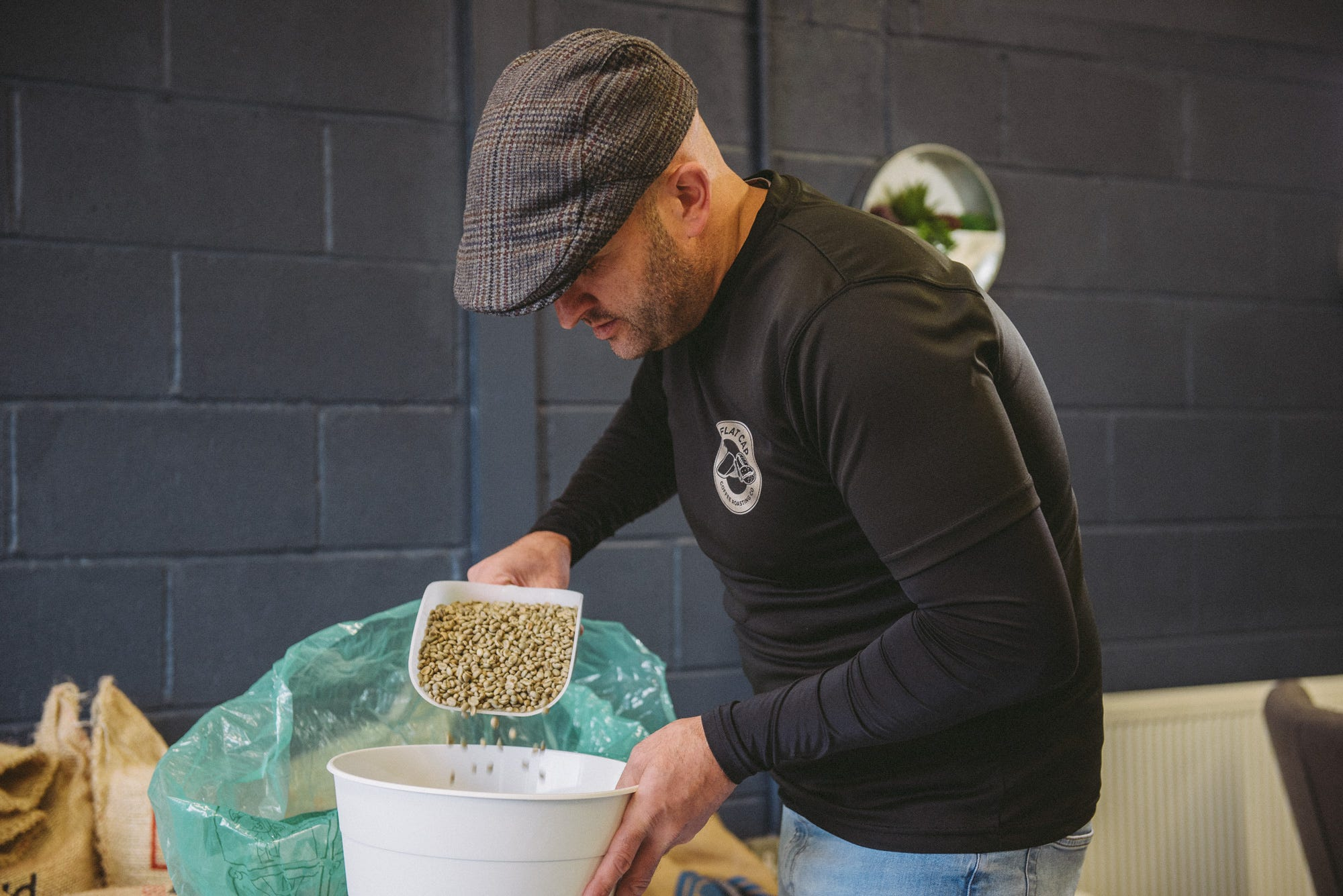 Mark of Flat Cap Coffee Roasting Co. pouring coffee beans into a drum
