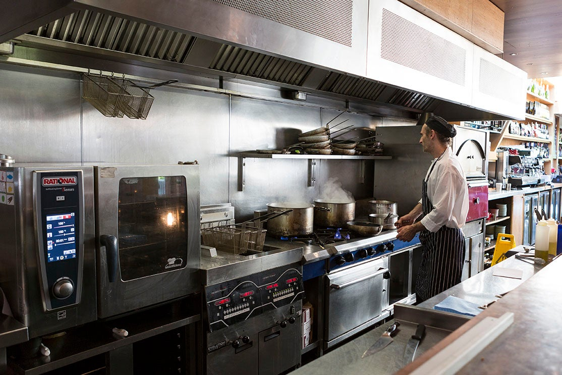 A chef cooks using pan on a commercial cooking range