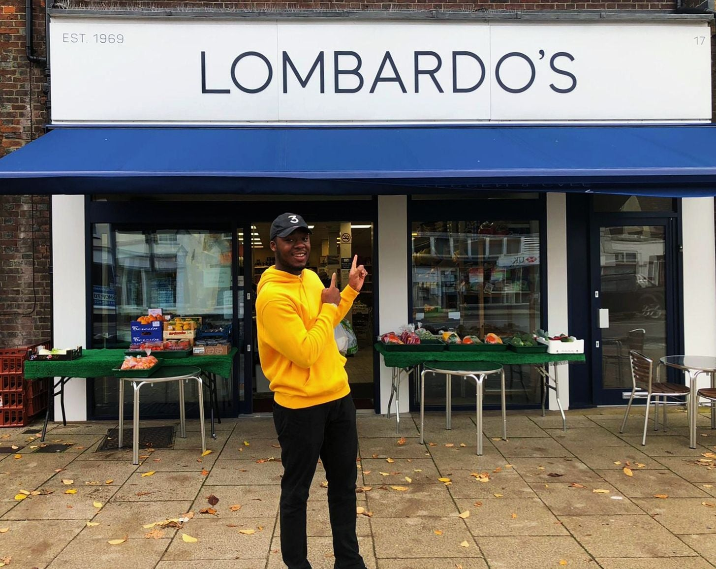 Bobby wearing a yellow hoodie and stood outside Lombardo's cafe