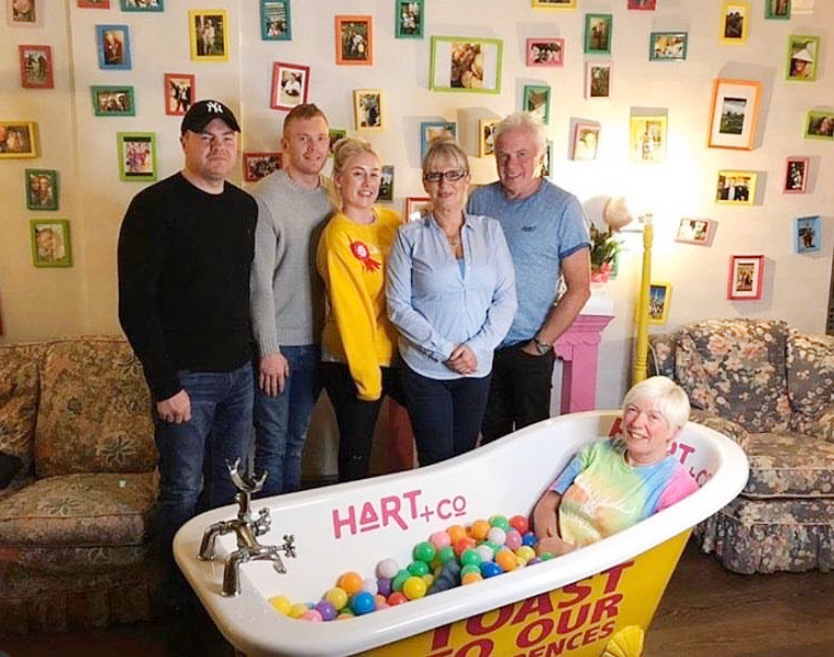 Five members of the HART restaurant team stand in front of a bathtub that has a sixth team member in.