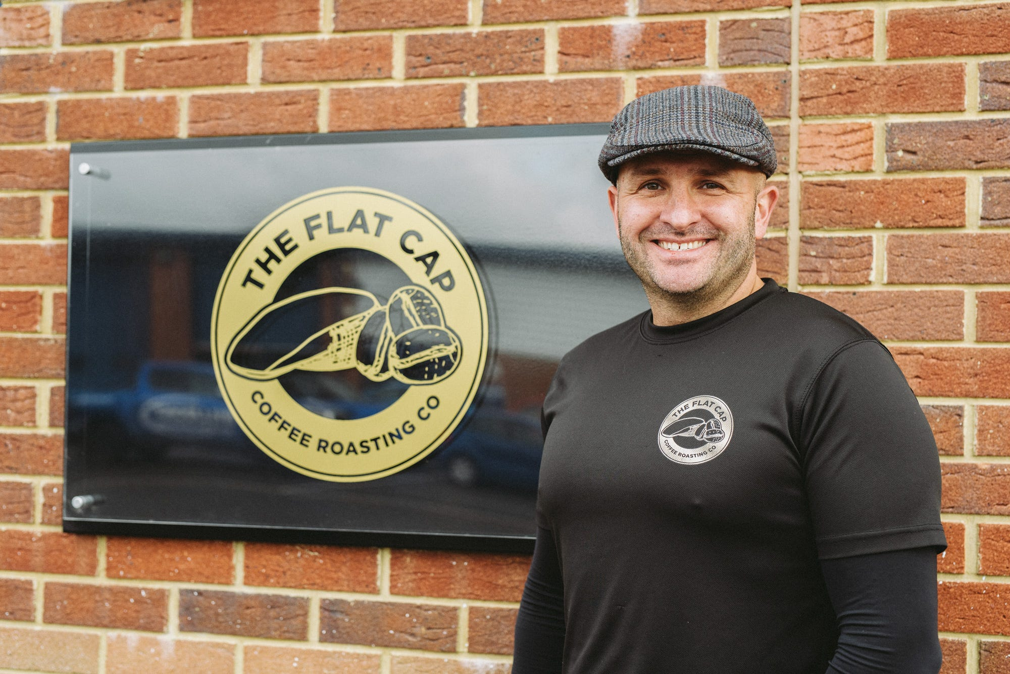 Mark Hepworth standing next to wall displaying Flat Cap Coffee Roasting Co. sign