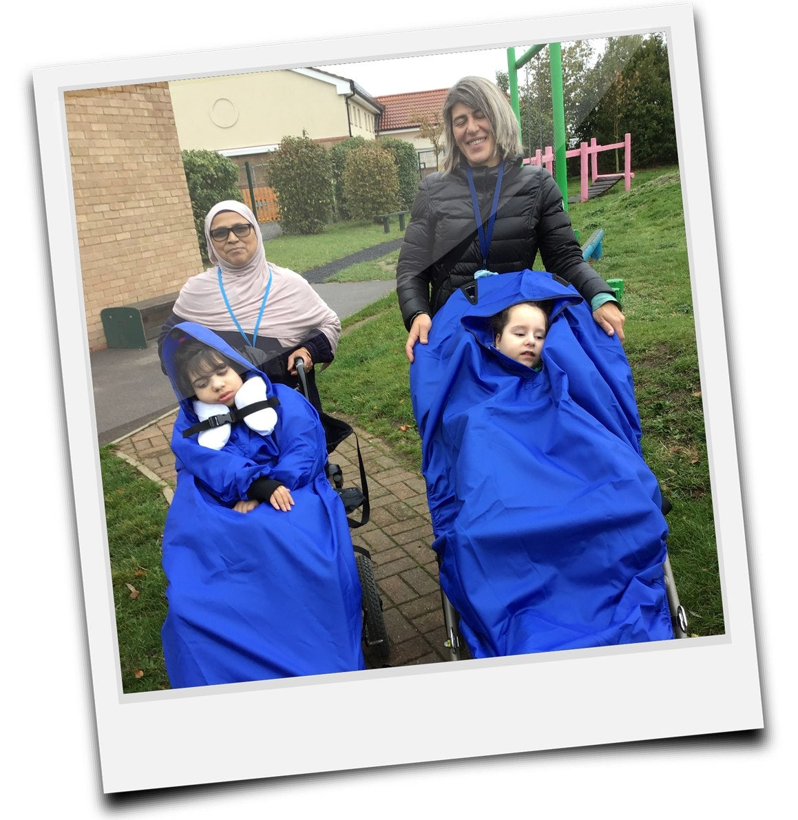 Two children wrapped up snugly in the donated wheelchair ponchos