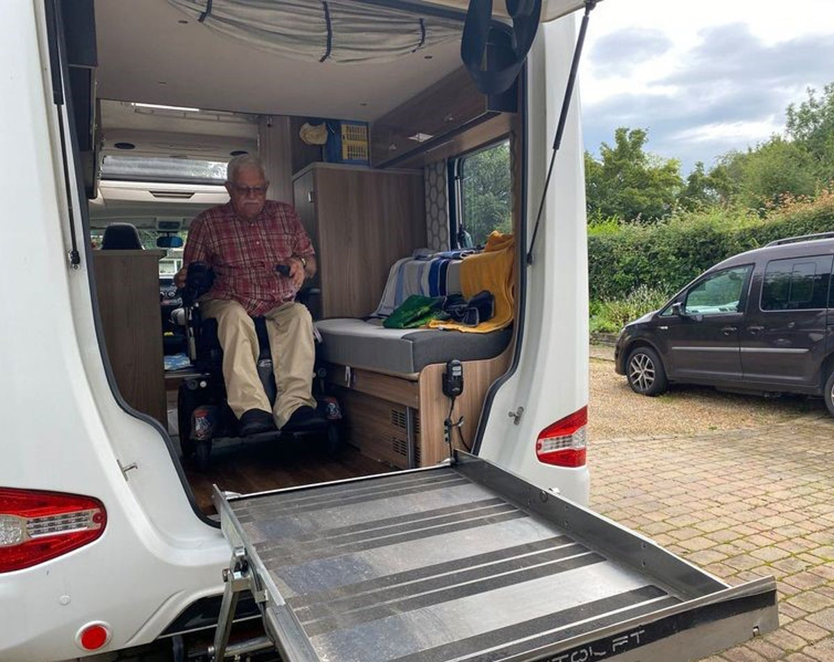 The customer moving the wheelchair down the aisle of the motor home to see if it fits