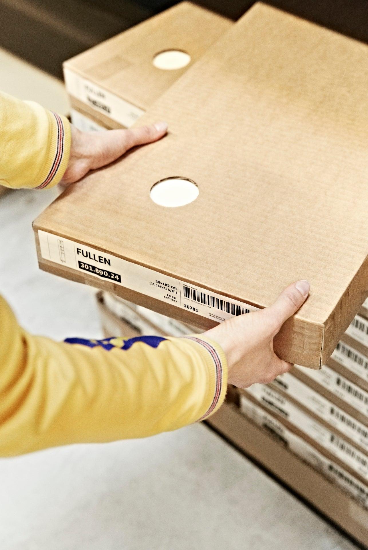 An IKEA worker picks up a flatpack box