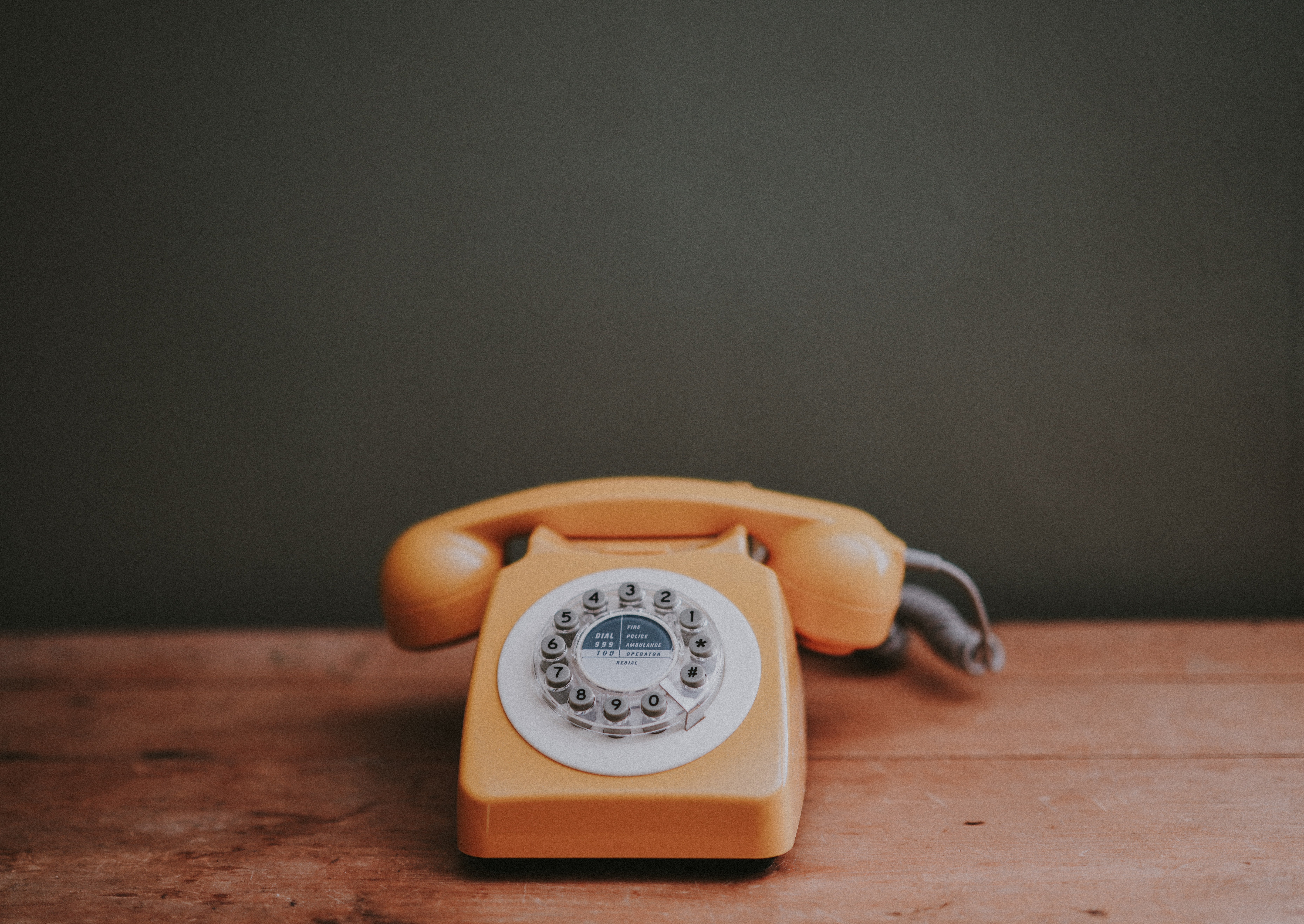 A photograph of an old-looking rotary phone