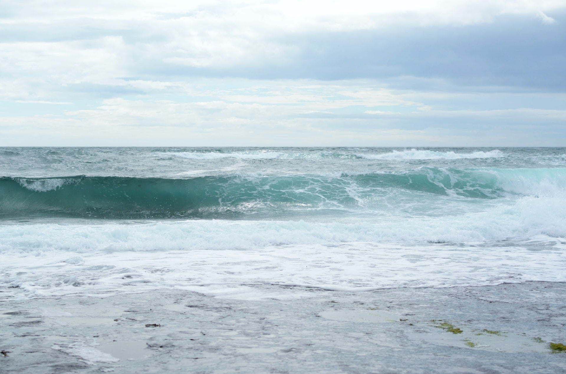 A view of the open sea, and a wave cresting