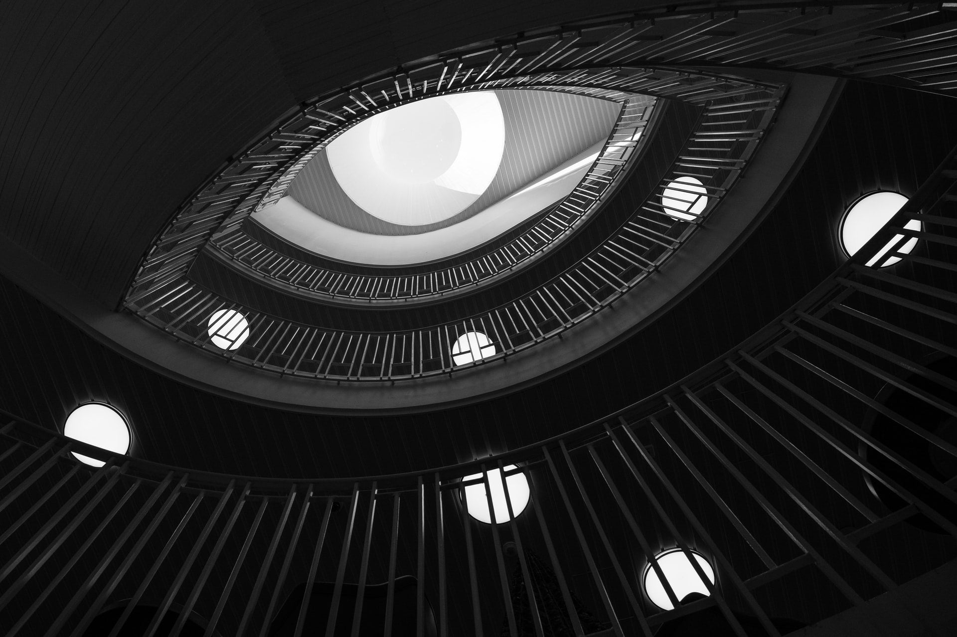 The camera is pointing up from the foot of a spiral staircase. The way the staircase curves make the vision resemble a human eye