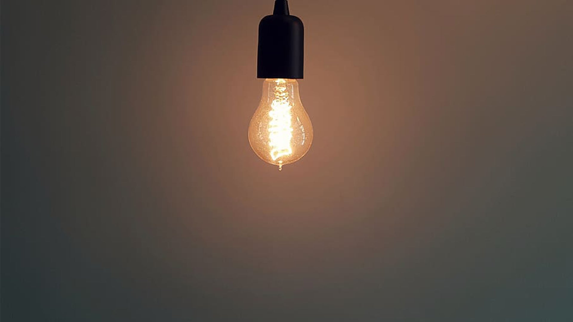 A picture of a glowing bulb suspended by a cord above the edge of the photograph