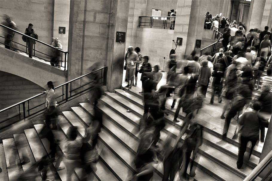 A black and white picture taken at a high angle of some steps. Lots of people are ascending and descending, but details are blurry so we can't see their faces.