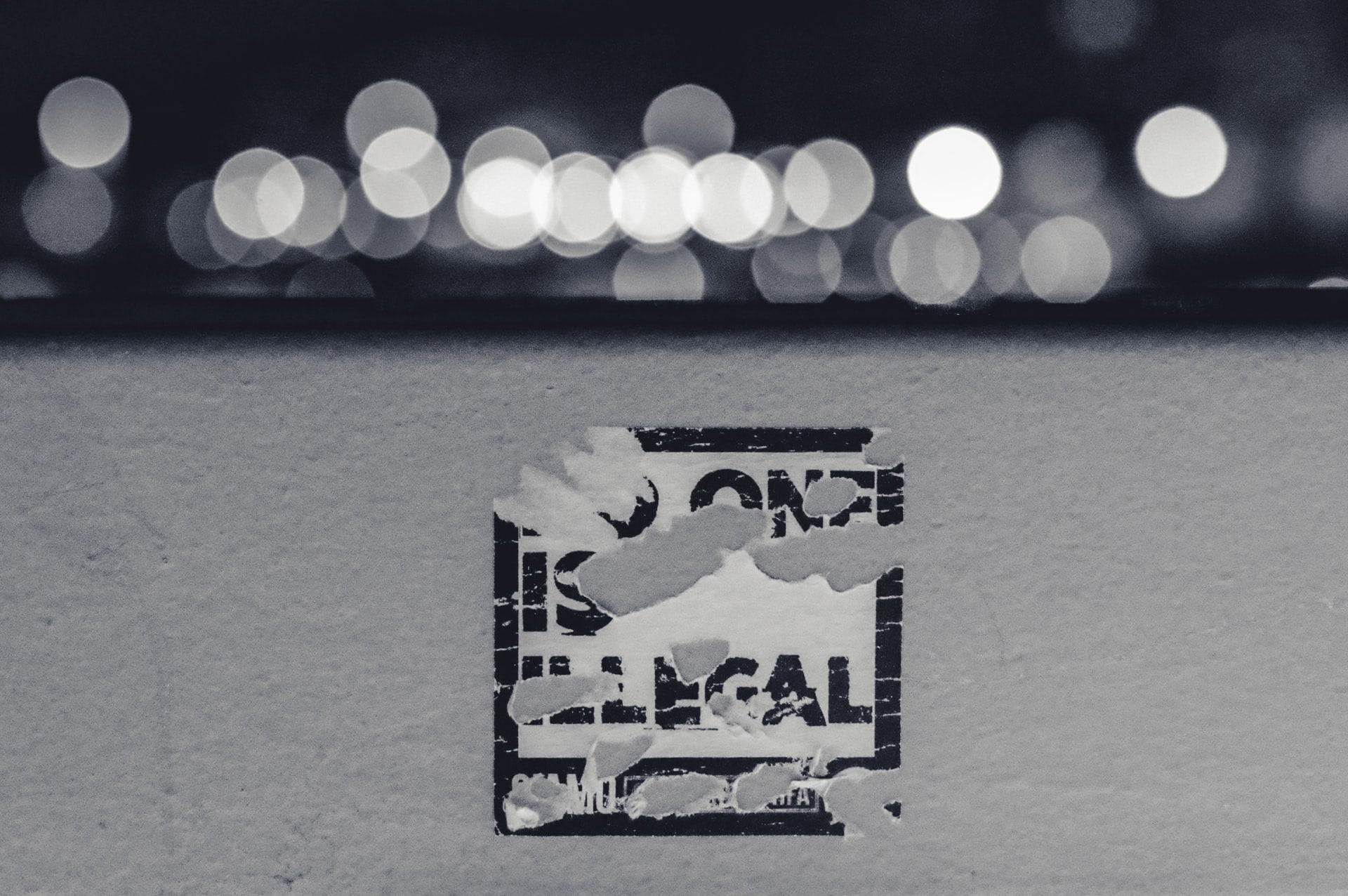 A photograph of a sticker on a wall. Much of it has been peeled away, but the words 'no one is illegal' can still be made out