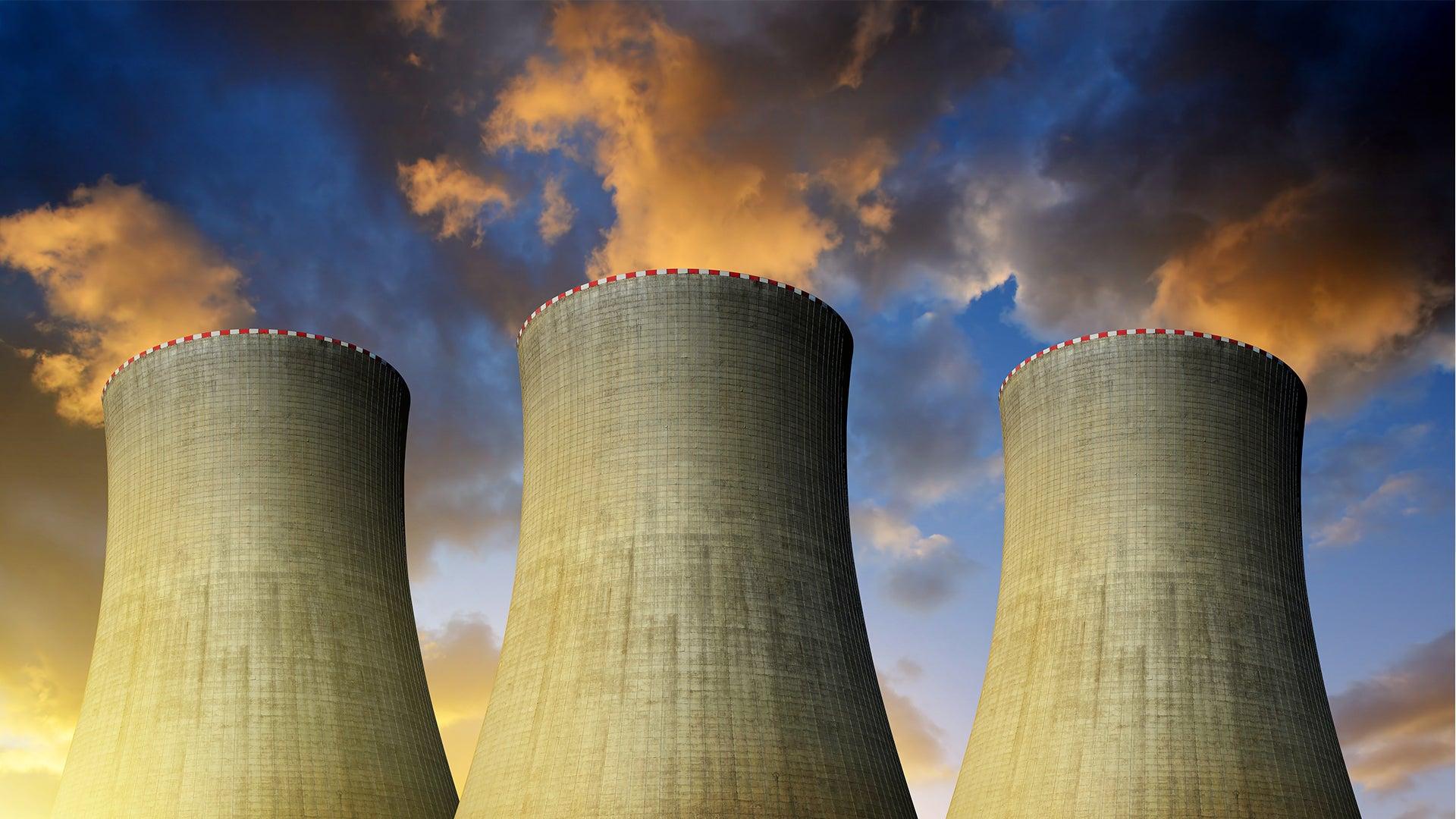Three massive industrial chimneys expelling fumes