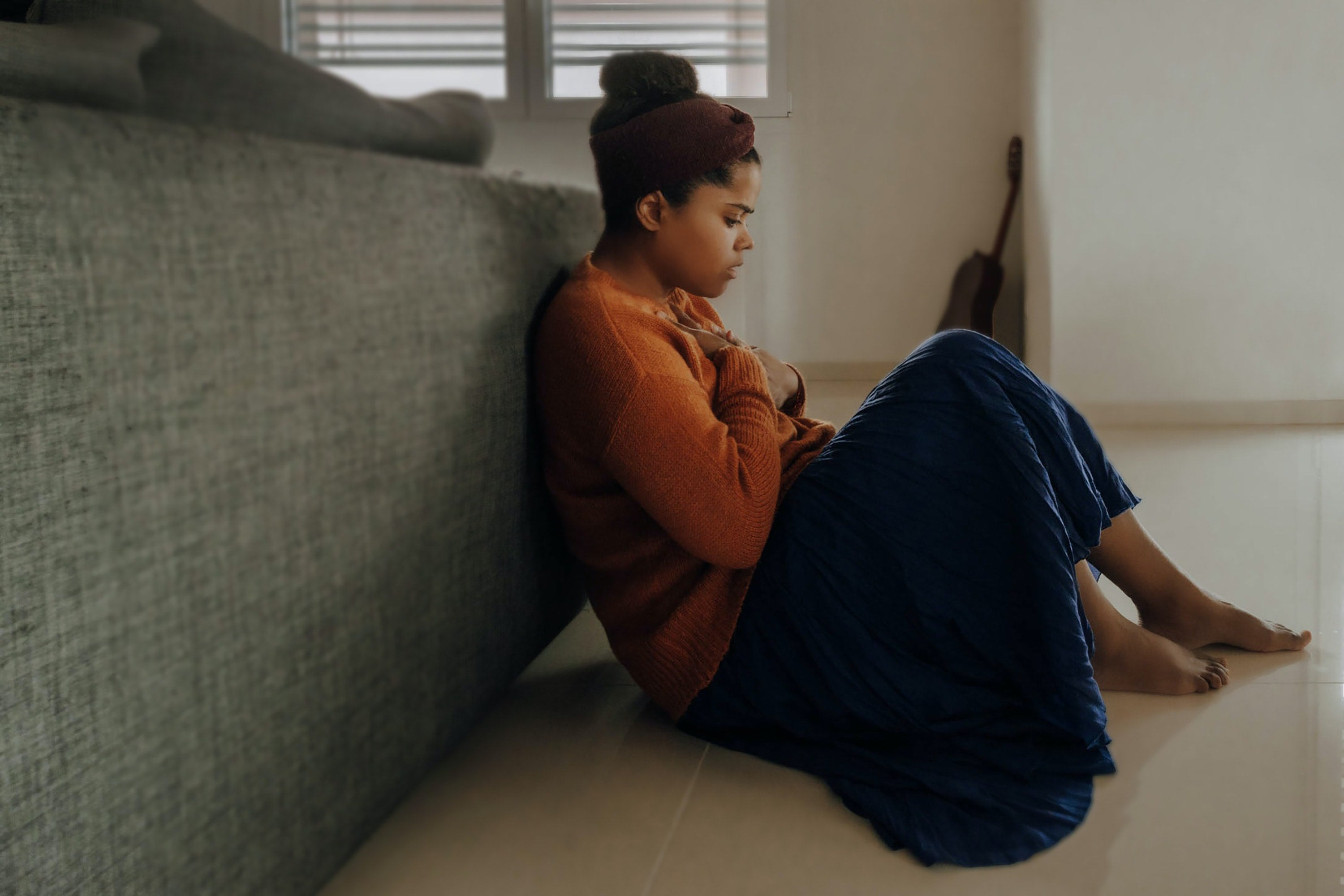 a woman sits on the floor embracing herself sadly