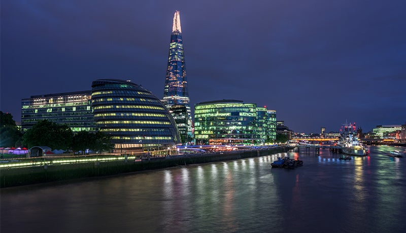 A photo taken from the Thames in London, looking towards The Shard and surrounding glass-fronted buildings
