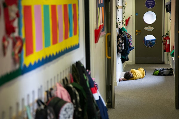 Don't exclude me - a boy lays on the corridor floor. Copyright BBC