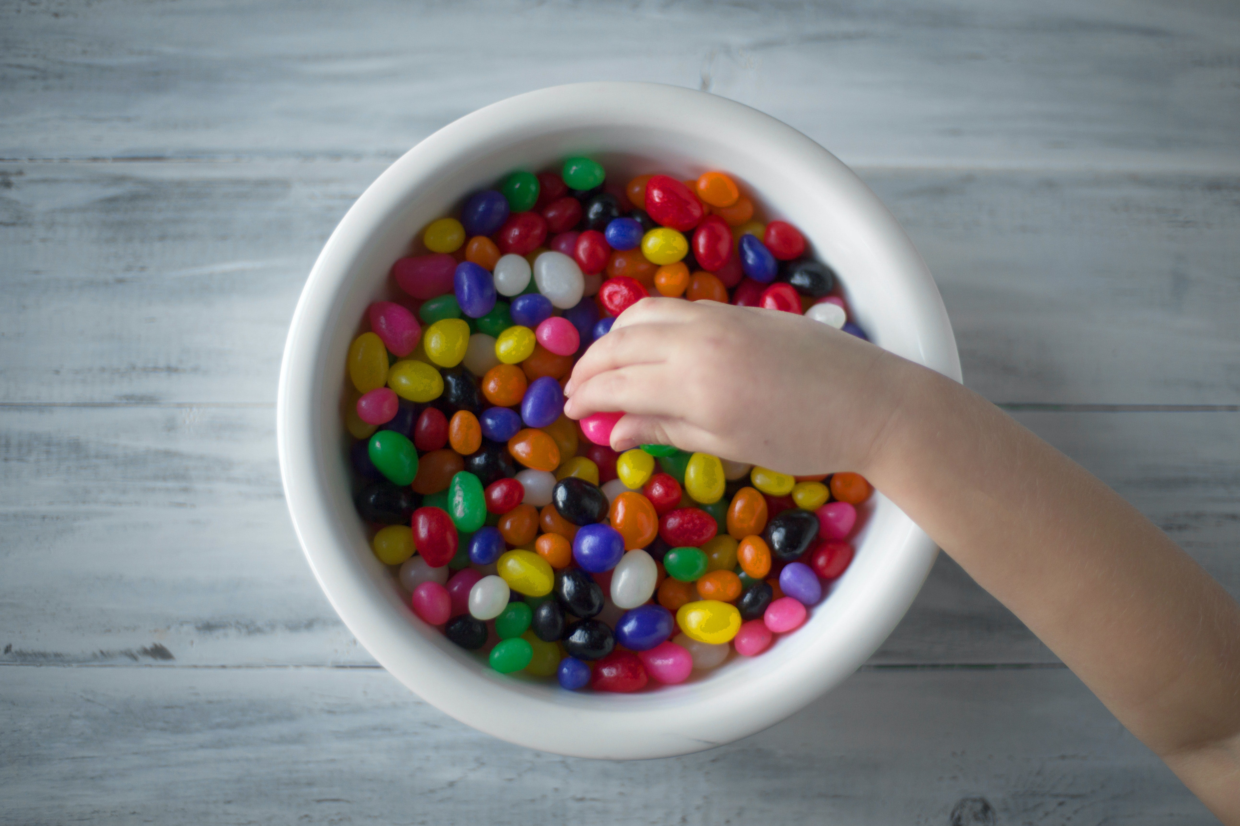 Child grabbing colourful sweets jelly beans