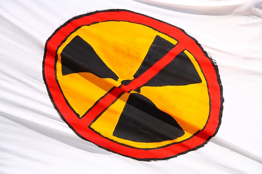 """A white flag with a yellow and black nuclear symbol on it, and a red """"banned"""" sign painted over the top."""