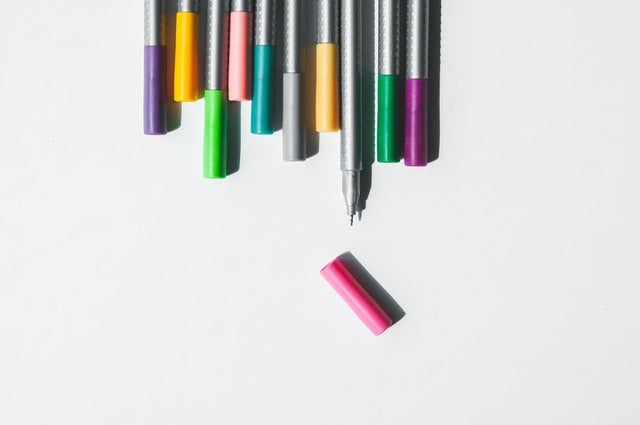 A row of coloured pens all lined up