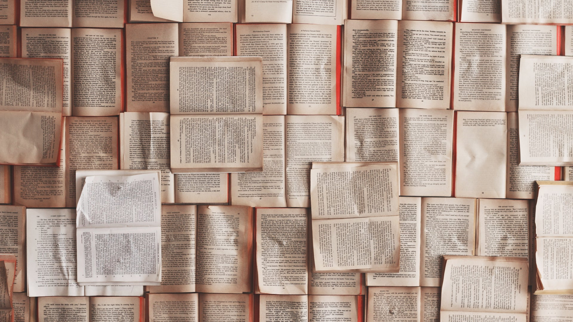 The whole picture frame is full of books, arranged in a rough grid and laid open with their pages overlapping one another