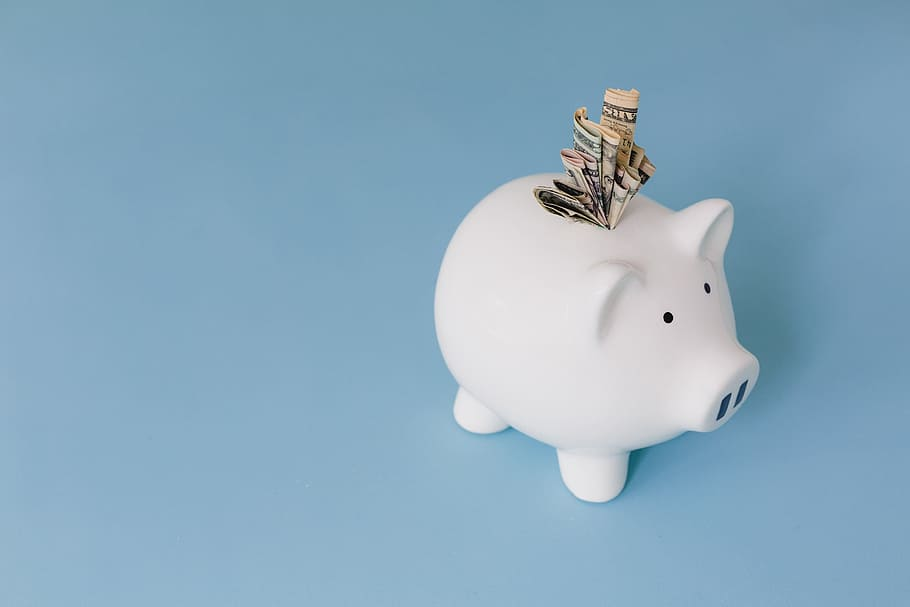A white 'piggy bank' on a blue surface. A wad of bills are sticking out of the slot in its back