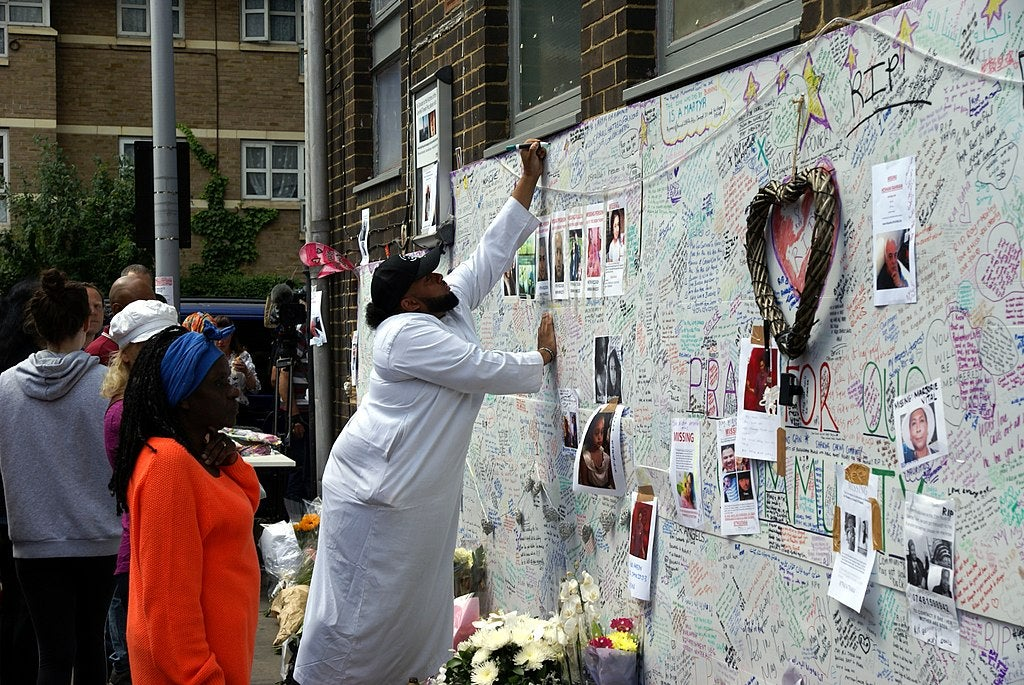 Community member writing on Grenfell tribute wall