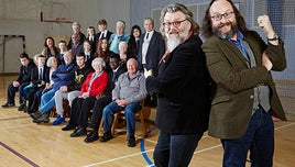 Dave Myers and Si King posing in a school hall, with programme contributors in the background.