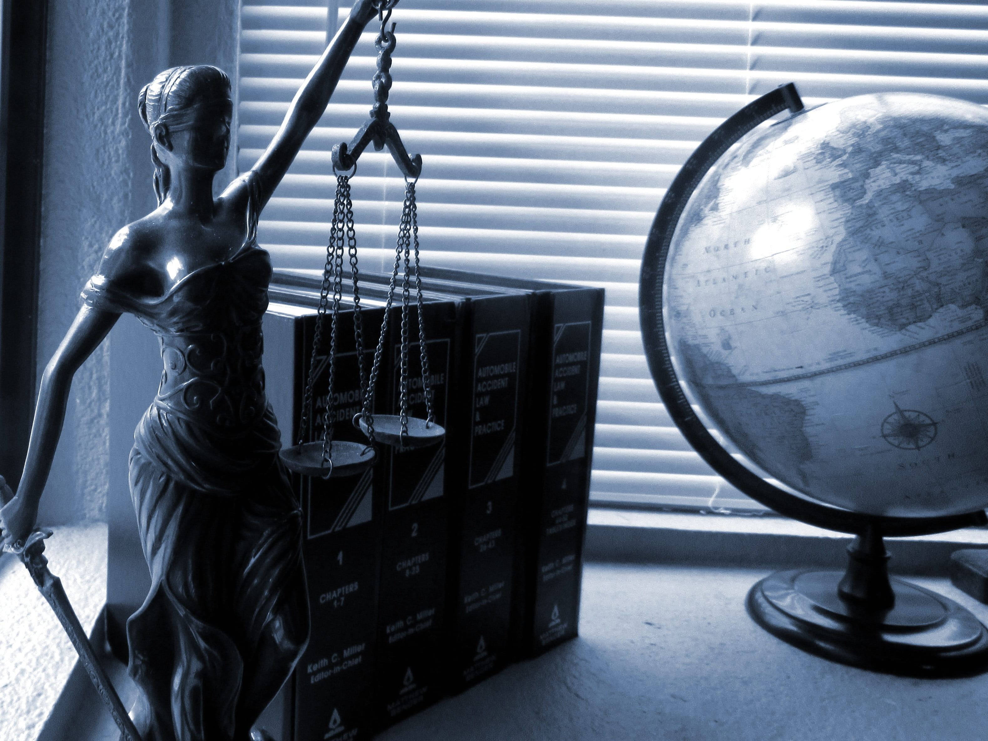 A greyscale photo featuring a model of the scales of justice next to a globe
