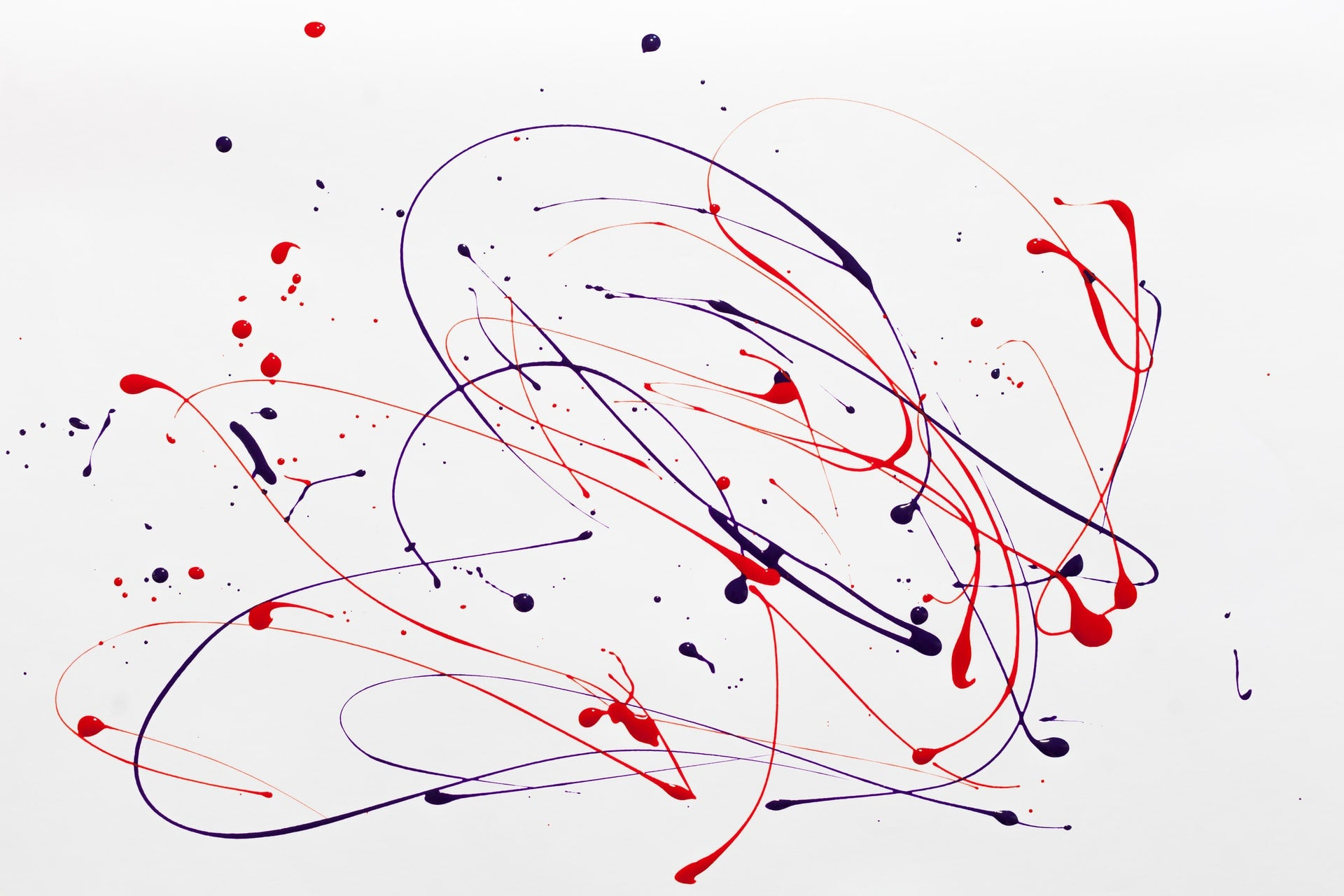 Red and blue streaks of paint form an abstract painting on a white surface